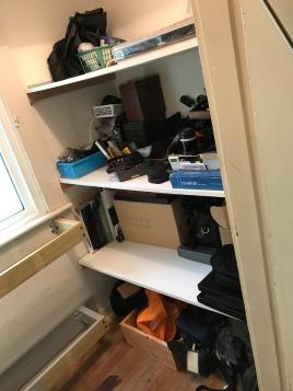 Disorganized shelves opposite bag wall